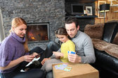Family gathered by the fire place playing cards — Stock Photo