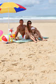 Family sat on the beach by parasol — Stock Photo