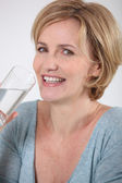 Closeup of healthy woman drinking a glass of pure water — Stock Photo