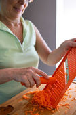 Woman grating a carrot — Stock Photo