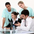 Medical staff gathered by desk — Stock Photo