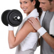 Stock Photo: Young couple exercising with a dumbbell