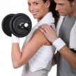 Foto Stock: Young couple exercising with dumbbell