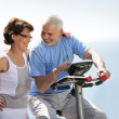 Senior couple with an exercise bike — Stock Photo