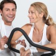 Couple at the gym on cycling machine — Stock Photo
