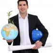 Architect holding globe and plans — Stock Photo #11895705