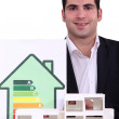 Architect posing near model shows house with energy rating - Stock Photo