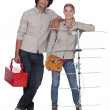 Couple stood with television aerial - Stock Photo