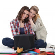Female students sitting on floor with laptop — Stock Photo #11898888