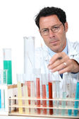 50 years old scientist in a lab behind test tubes — Stock Photo