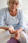 Elderly woman taking a pill — Stock Photo