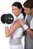Young couple exercising with a dumbbell — Stok fotoğraf