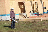 Foreman stood by unfinished wooden house — Stock Photo