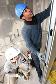 Two handymen fitting plasterboard — Stock Photo