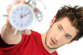 A frazzled man holding an alarm clock — Stock Photo