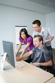 Dynamic trio working at a desktop computer — Stock Photo