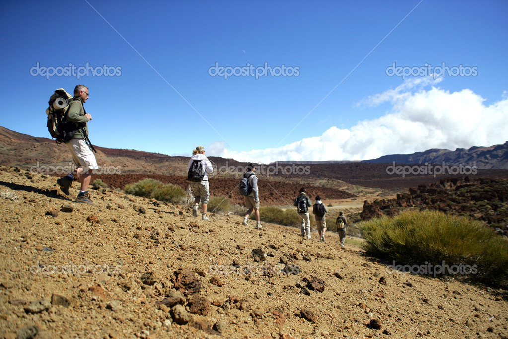 Tourist group walking in an arid landscape — Stock Photo #11894456