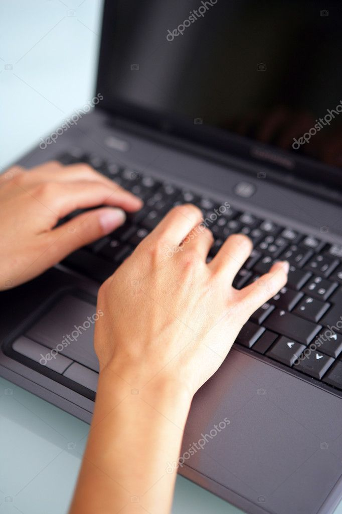 Woman tying on a laptop  Stock Photo #11896010