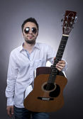 Young man with acoustic guitar — Stock Photo