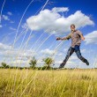 Young man jumping on dry meadow — Stock Photo #11760804