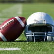 Stock Photo: American Football and Helmet on the Field