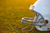 American Football Helmet on Field Backlit — Stock Photo
