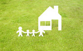 Family home of paper cut on grass background — Stock Photo