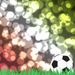Football with green grass on color abstract background — Stock Photo #11737587