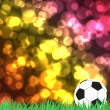 Stock Photo: Football with green grass on color abstract background