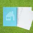 Book with home icon on grass background — Stock Photo