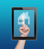 Hand pushing home button of tablet on a touch screen — Stock Photo
