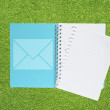 Stock Photo: Book with mail on grass background