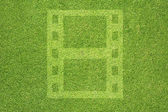 Film on green grass texture and background — Stock Photo