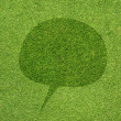 Comment icon on green grass texture and background — Stock Photo #12185852