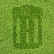 Trash icon on green grass texture and background — Stok Fotoğraf #12194759