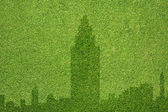 City icon on green grass texture and background — Stock Photo