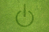 Shutdown icon on green grass texture and background — Stock Photo
