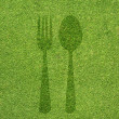 Fork and spoon icon on green grass texture and  background — Lizenzfreies Foto