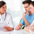 Doctor consults a young couple - Stock Photo