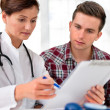 Doctor with male patient - Stock Photo