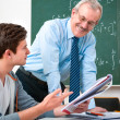 Student with teacher in classroom — Stock Photo #12365425