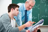 Student mit einem lehrer im klassenzimmer — Stockfoto