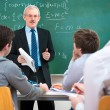 Teacher with students in classroom — Stock Photo #12386876