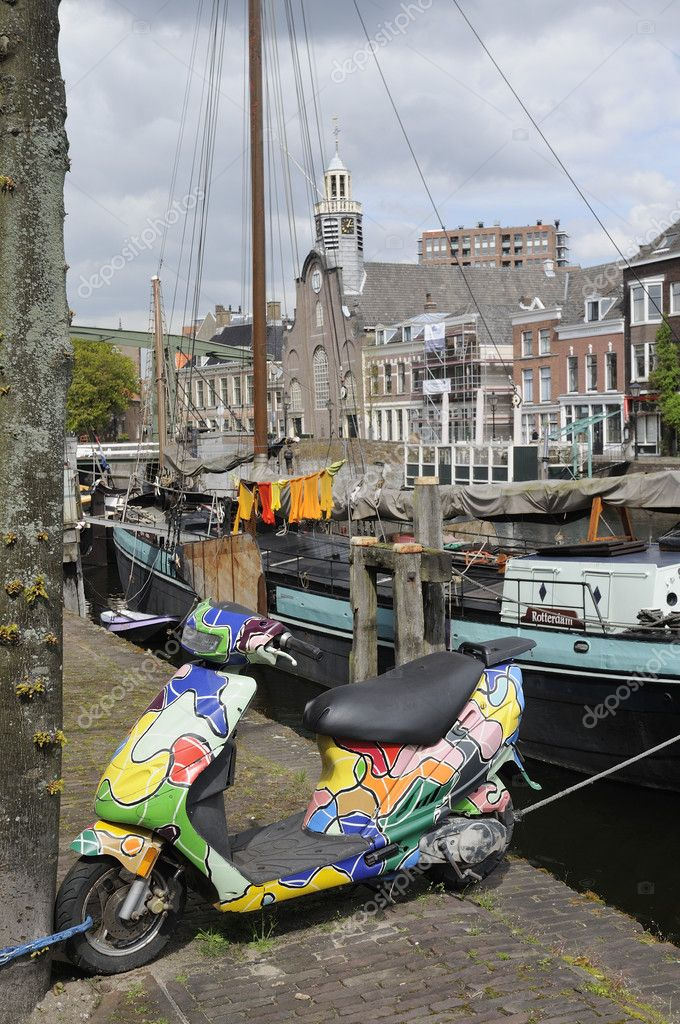 Foreshortening of picturesque canal with old boats and traditional houses, in foreground an hippy style colorful decorated scooter — Stock Photo #10802271