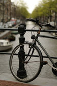 Old bike on canal, amsterdam — Stock Photo