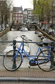 アムステルダムの運河沿いの青い自転車 — ストック写真