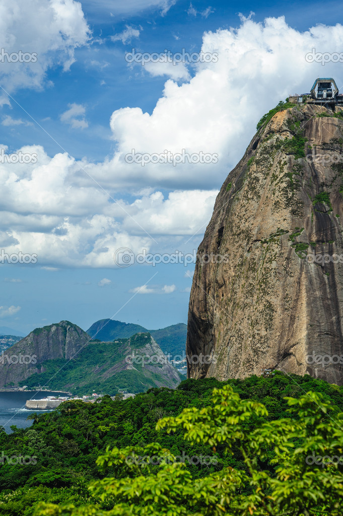Sugarloaf Mountain (in Portuguese, Po de Acar), is a peak situated in Rio de Janeiro, Brazil, at the mouth of Guanabara Bay on a peninsula that sticks out into the Atlantic Ocean.  Stock Photo #11478993