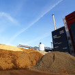 Stock Photo: Power plant with storage of wooden fuel against blue sky