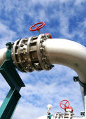 Industrial pipelines and valve with a natural blue background — Stock Photo