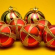 Christmas balls on yellow background — Zdjęcie stockowe